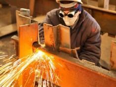 worker using torch cutter to cut through metal